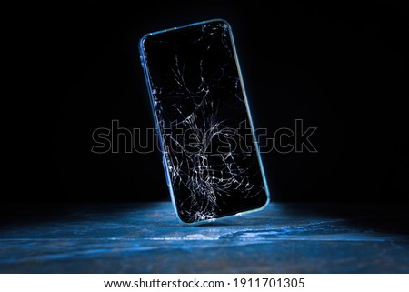 Mobile cellphone with broken glass. Smartphone falling down on the ground and broke touchscreen with beauty blue backlight and dark background Royalty-Free Stock Photo #1911701305