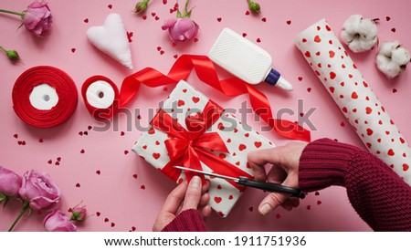 Step 12.Step-by-step instructions for wrapping gifts for Valentine's Day. Woman wraps a gift with wrapping white paper in heart and seals the edges with glue on a pink background top view, flat lay. Royalty-Free Stock Photo #1911751936