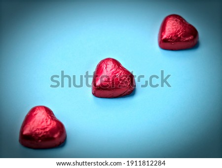 Three heart shaped chocolates in red tinfoil, in perspective and vignetted.