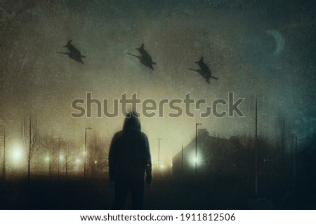 A man watching three witches on broomsticks flying across the sky in a city on a spooky winters night. With a grunge, abstract edit. Royalty-Free Stock Photo #1911812506