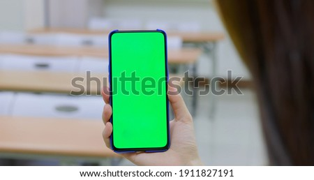 asian woman use green screen smartphone in the classroom at school