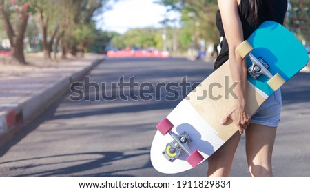 Close up on young women hand hold skateboard, surf skate on public park background. Free relax skateboard trendy concept. Fashion portrait of female hands holding surf skateboard