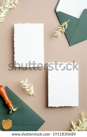 Flat lay wedding invitation cards, green envelope with seal wax stamp, dried flowers on pastel beige background. Wedding stationery set top view. Royalty-Free Stock Photo #1911830680