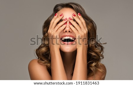 Beautiful woman with curly hair and red nails manicure . Girl happy  laughs  closes her face with a hand . Royalty-Free Stock Photo #1911831463