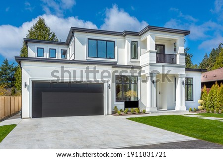 Beautiful contemporary white house with lush grass and blue sky twilight and daylight Royalty-Free Stock Photo #1911831721