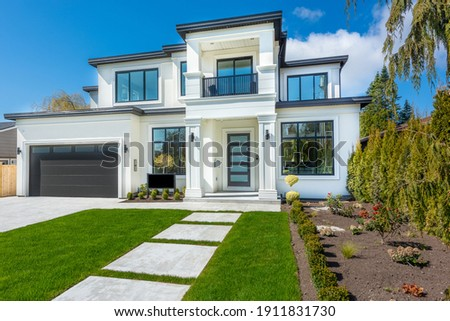 Beautiful contemporary white house with lush grass and blue sky twilight and daylight Royalty-Free Stock Photo #1911831730