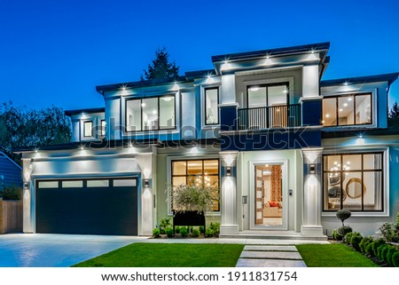 Beautiful contemporary white house with lush grass and blue sky twilight and daylight Royalty-Free Stock Photo #1911831754