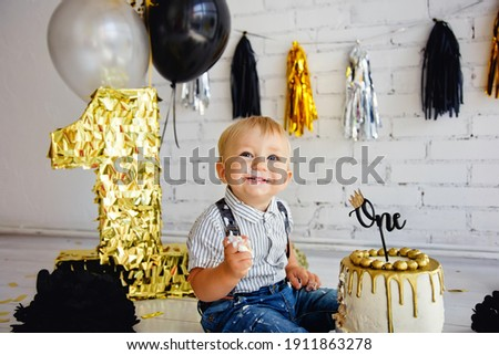 Happy boy blonde 1 year old on his birthday tries sweets. The photo zone with the first cake is decorated in black and gold. Crashcake Royalty-Free Stock Photo #1911863278