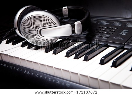 Headphones on musical synthesizer keyboard. Headphones on electronic piano Royalty-Free Stock Photo #191187872