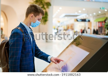 young man in the mall looks at the monitor in a mask