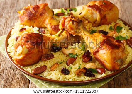 Homemade Arabic spiced rice and chicken topped with nuts, raisins closeup in the plate on the table. horizontal  Royalty-Free Stock Photo #1911922387