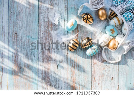 Gold, black, white, blue  eggs in a string bag on a blue wooden background. Geometry. The minimal concept. Top view. An Easter card with a copy of the place for the text. Royalty-Free Stock Photo #1911937309