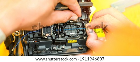 Banner template Technician Fiberoptic Fusion Splicing. Worker connecting for Cable Internet signal and Wire connection with Fiber Optic Fusion Splicing machine,fiber optic cable splice machine in work Royalty-Free Stock Photo #1911946807