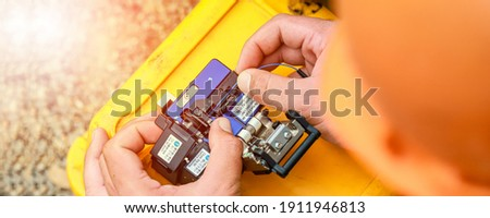 Banner template Technician Fiberoptic Fusion Splicing. Worker connecting for Cable Internet signal and Wire connection with Fiber Optic Fusion Splicing machine,fiber optic cable splice machine in work Royalty-Free Stock Photo #1911946813