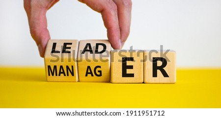 Manager versus leader symbol. Businessman flips wooden cubes and changes the word 'manager' to 'leader'. Beautiful white background, copy space. Business and manager versus leader concept. Royalty-Free Stock Photo #1911951712