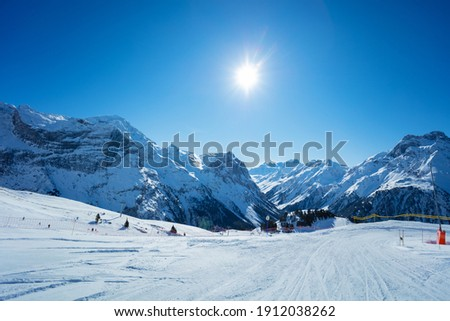 Mountain peaks and clean empty ski trails in Pralognan-la-Vanoise range over snowy tops in French Alps Royalty-Free Stock Photo #1912038262