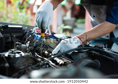 A mechanic is repairing a car about the engine's valve system. Royalty-Free Stock Photo #1912050442