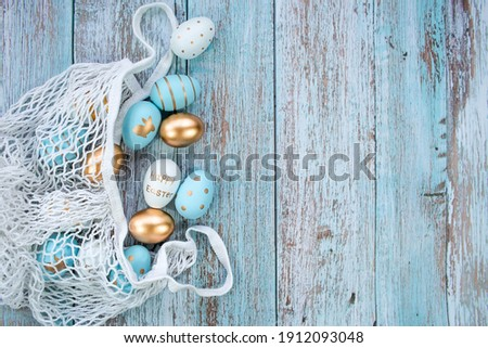 Gold, black, white, blue  eggs in a string bag on a blue wooden background. Geometry. The minimal concept. Top view. An Easter card with a copy of the place for the text. Royalty-Free Stock Photo #1912093048