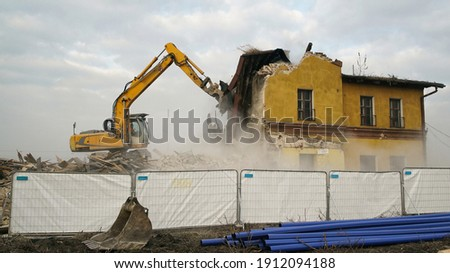 Yellow excavator destroys an old building. Heavy duty machine is demolishing a brick building.  Royalty-Free Stock Photo #1912094188