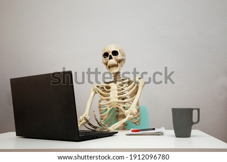 Bored at work: dead skeleton working at its home office.