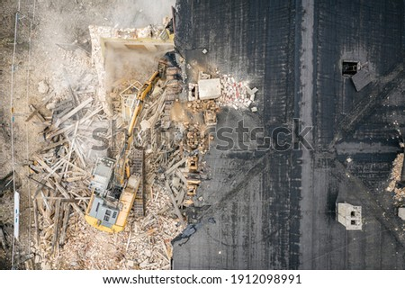 Yellow excavator destroys building. Heavy duty machine is demolishing a brick building. Demolition of the building . Demolition construction work aerial drone photo view Royalty-Free Stock Photo #1912098991
