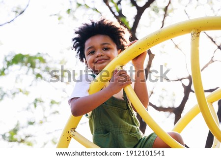 Cute African American little kid boy having fun while playing on the playground in the daytime in summer. Outdoor activity. Playing make believe concept. Outside education Royalty-Free Stock Photo #1912101541