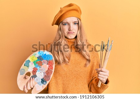 Beautiful young caucasian girl holding paintbrush and painter palette depressed and worry for distress, crying angry and afraid. sad expression.