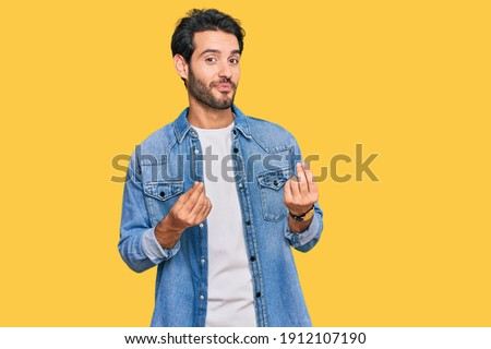 Young hispanic man wearing casual clothes doing money gesture with hands, asking for salary payment, millionaire business  Royalty-Free Stock Photo #1912107190