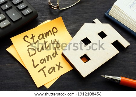 Stamp duty land tax SDLT memo and model of home. Royalty-Free Stock Photo #1912108456