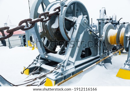 The mooring deck of a cargo ship with anchor winches, an anchor chain on winches, bollards and haws with mooring ropes, frozen and covered in snow. Snow on the mooring deck of a cargo ship. Royalty-Free Stock Photo #1912116166
