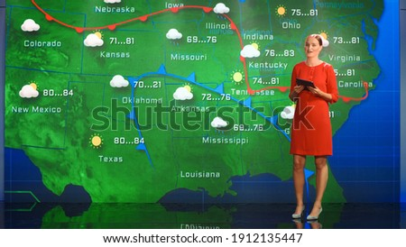 Live Weather News Studio with Professional Female On-Camera Meteorologist Standing Beside Screen and Making Gestures to Point at Weather Synoptic Map Chart for United States of America Royalty-Free Stock Photo #1912135447
