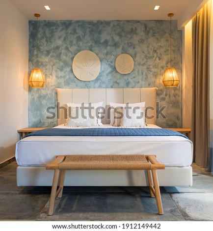 Front view of modern bedroom interior in nautical marine style with blue decorative stucco wall, wicker furniture, ceiling wooden lamps, white soft bed Royalty-Free Stock Photo #1912149442