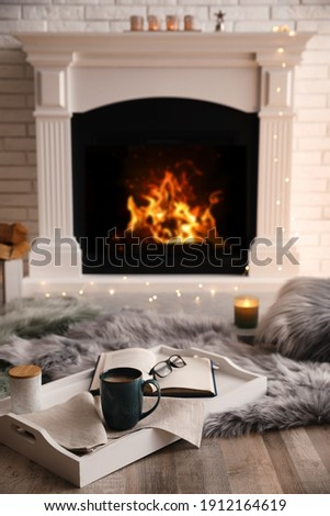 Cup of coffee, glasses and book on tray near fireplace indoors. Cozy atmosphere Royalty-Free Stock Photo #1912164619