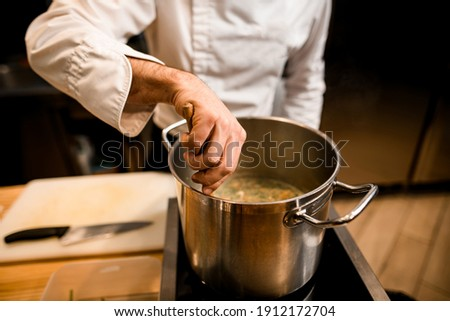 close-up on the hand of male chef in white jacket who is stirring soup in pot with spoon