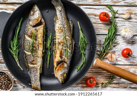 BBQ sea Bass fish, fried sea bass in a pan. White wooden background. Top view Royalty-Free Stock Photo #1912265617