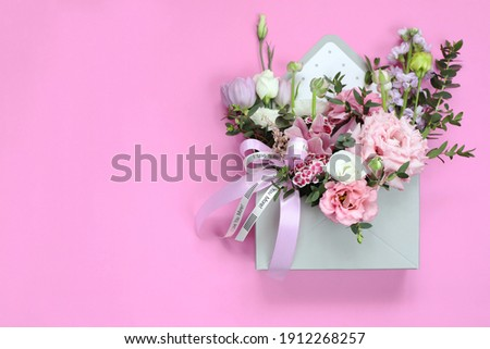 Bouquet as a gift for the holiday of March 8, St. Valentine's Day, mother's day, birthday, wedding day. Floral arrangement of tulips, eustoma, ranunculus, orchids, chrysanthemums, eucalyptus branches. Royalty-Free Stock Photo #1912268257