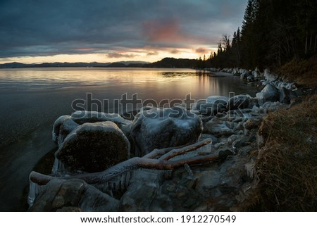 Icy frozen shore of the lake in sunset time. Jonsvatnet lake near Trondheim in Norway. Beautiful sunset colors on the sky and clouds. Ice patterns and texture. Frosty winter time. Royalty-Free Stock Photo #1912270549