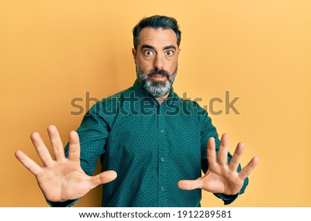 Middle age man with beard and grey hair wearing business clothes afraid and terrified with fear expression stop gesture with hands, shouting in shock. panic concept.  Royalty-Free Stock Photo #1912289581