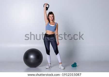 Athletic woman exercising with kettlebell standing lifting it up her head on white background isolated. Trainer show muscle workout with weights to strength biceps