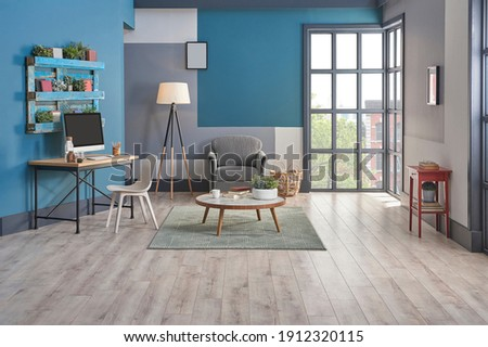 Decorative blue and grey wall background, home decoration interior style with sofa carpet middle table frame and working desk style.