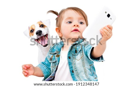 Little cute girl makes selfie with  dog Jack Russell Terrier on phone isolated on white background Royalty-Free Stock Photo #1912348147