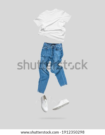 White flying cotton T-shirt, blue jeans, white leather sneakers isolated on gray background. Clean white Unisex T-shirt. Branding clothes. Mock up for your design. Spring Summer Women's Clothing Royalty-Free Stock Photo #1912350298