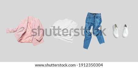 White flying cotton T-shirt, blue jeans, white leather sneakers, fashionable pink blazer jacket isolated on gray background. Clean Branding clothes. Mock up for your design. Spring Summer Clothing Royalty-Free Stock Photo #1912350304