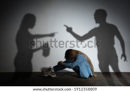 Domestic physical violence, abusing. Scared little caucasian girl, victim sitting close to white wall with shadow of angry threatening parents with alcohol addiction. Awareness of social problem. Royalty-Free Stock Photo #1912358809