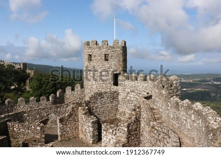 Medieval castle ruin stone tower of traditional historic Castelo dos Mouros, Castle of the Moors, ancient portuguese UNESCO tourist landmark on hill in Sintra near Lisbon (Lisboa), Portugal, Europe. Royalty-Free Stock Photo #1912367749
