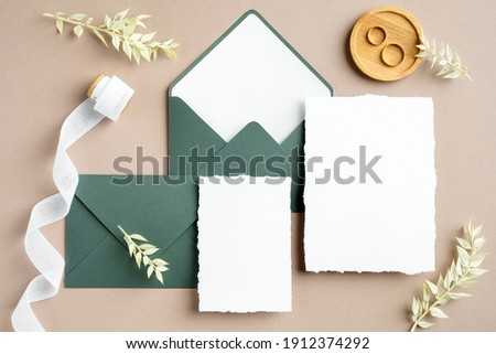 Elegant wedding stationery set. Wedding invitation cards templates, green envelopes, silk ribbon, golden rings on pastel beige background. Flat lay, top view, copy space. Royalty-Free Stock Photo #1912374292