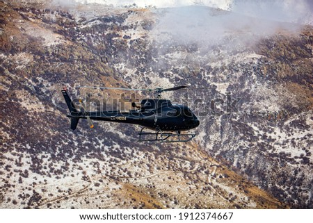 Helicopter in flight. Black Helicopter is flying between mountains peak, winter time. Luxury Lifestyle. Vacation tour on Helicopter Royalty-Free Stock Photo #1912374667