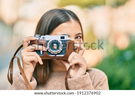 Young hispanic tourist woman smiling happy using vintage camera at the city. Royalty-Free Stock Photo #1912376902