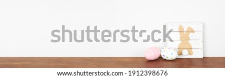 Easter decor on a wooden shelf. Rustic wood bunny sign with eggs  against a white wall banner. Copy space.