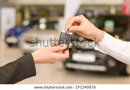 Female hand getting modern car key on several car background #191240876